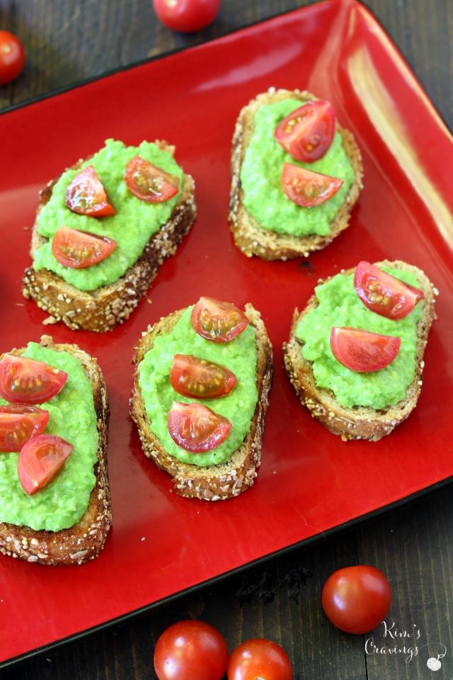 The joining of flavorful, light pea pesto spread over crusty bread and topped off with juicy cherry tomatoes makes this light pea pesto crostini appetizer a family favorite.