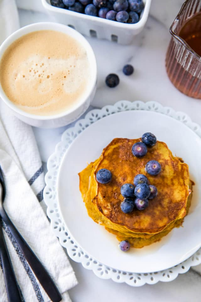 stacked pancakes topped with blueberries and served with frothy coffee