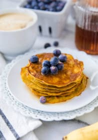 stack of thin pancakes on a white plate topped with blueberries and syrup