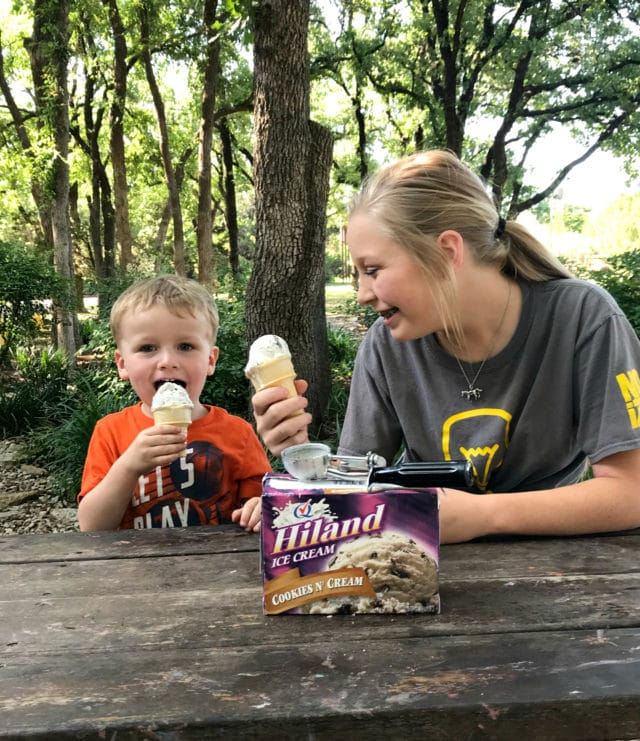 two kids enjoying ice cream cones sitting at a picnic table