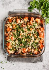 Mexican enchilada casserole topped with chopped fresh cilantro in a square glass baking dish