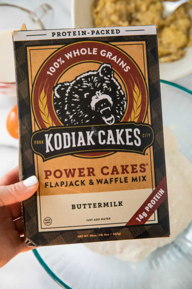 holding a box of Kodiak Cakes Power Cakes Mix