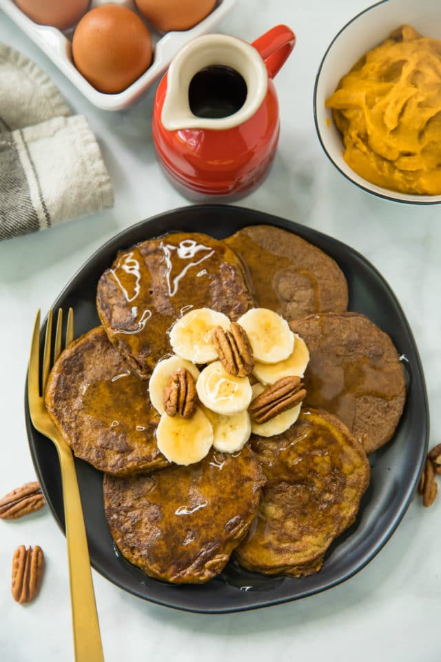 overhead photo of Flourless Pumpkin Pancakes topped with banana slices, pecan halves and maple syrup; served on a black plate with a gold fork and maple syrup on the side.