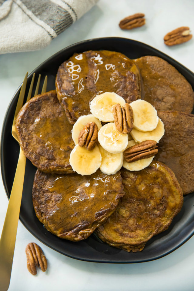 overhead photo of Flourless Pumpkin Pancakes topped with banana slices, pecan halves and maple syrup; served on a black plate with a gold fork