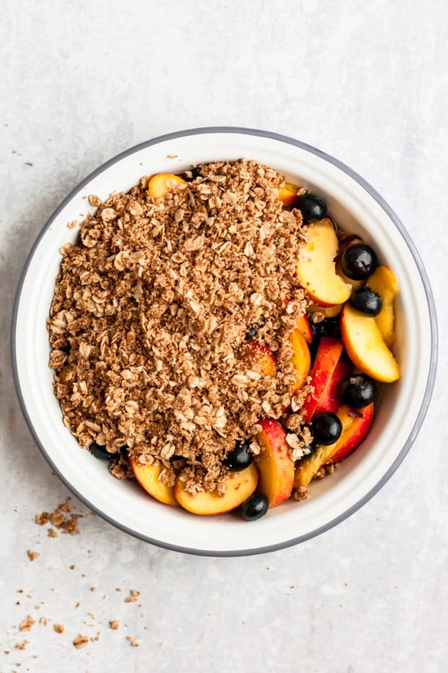 blueberry peach dessert with oat brown sugar topping in a white pie plate