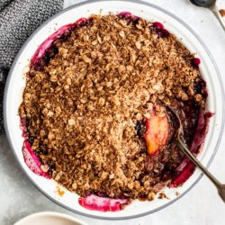 EasyPeach Blueberry Crisp in a white pie plate with a silver serving spoon