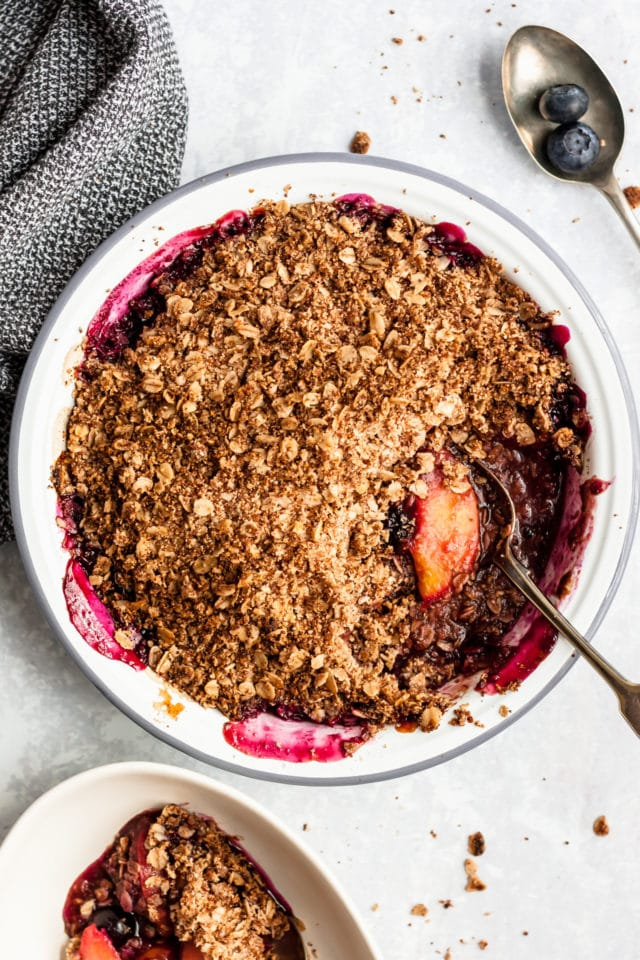Easy Peach Blueberry Crisp in a white pie plate with a silver serving spoon