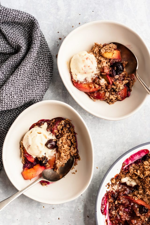 two servings of fruit crisp topped with ice cream in white bowls