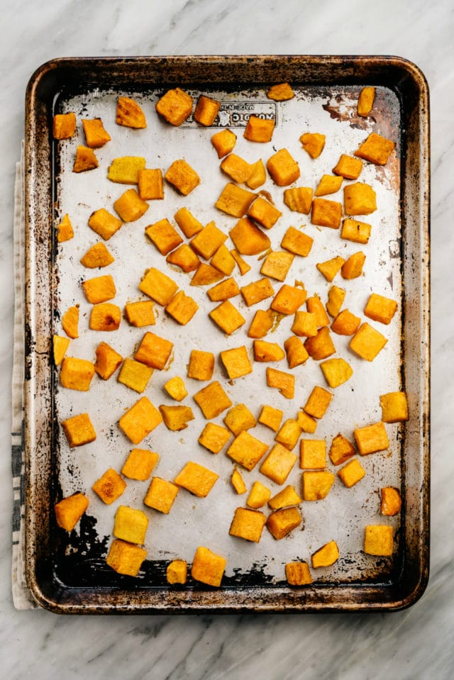 roasted cubed butternut squash on a sheet pan