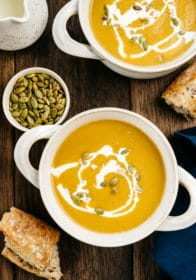 butternut squash soup served in white bowls with crusty bread