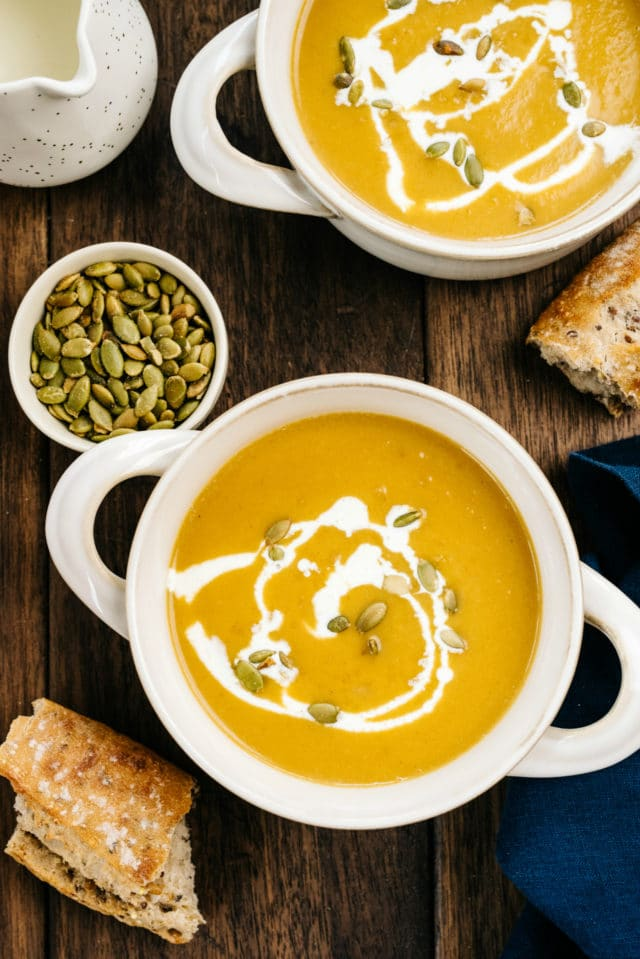 butternut squashsoup served in white bowls with crusty bread