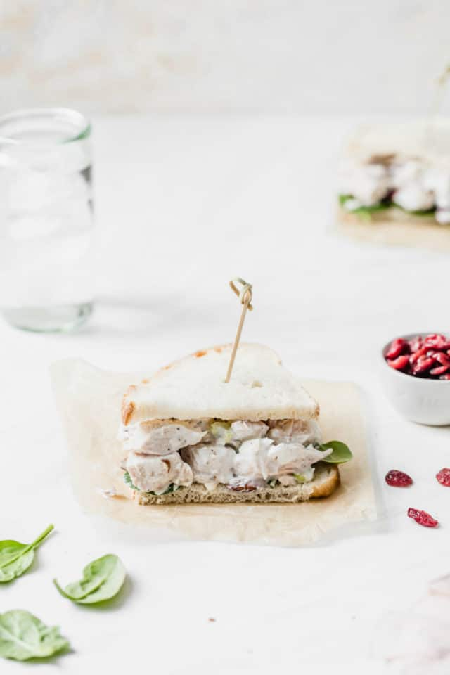 chicken salad sandwich on white bread served with a glass of water