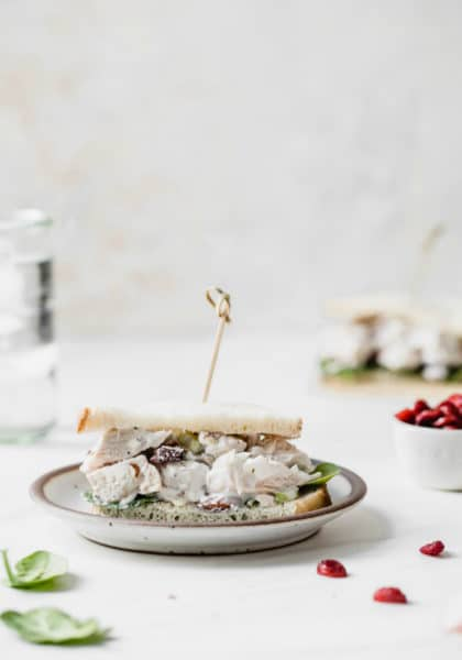 chicken salad sandwich made with Greek yogurt on a white plate with a glass of water