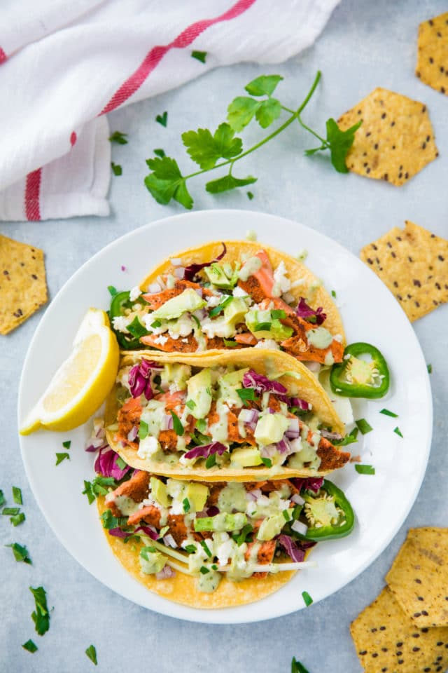 salmon tacos on a large white plate served with chips