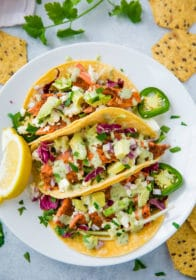 fish tacos topped with avocado and slaw on a white plate