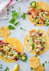 salmon and taco toppings on corn tortillas