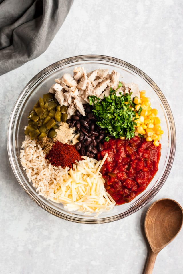ingredients for chicken enchilada casserole in a glass mixing bowl
