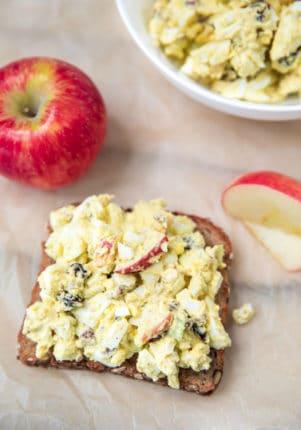 egg salad served on a slice of toast served with apple slices
