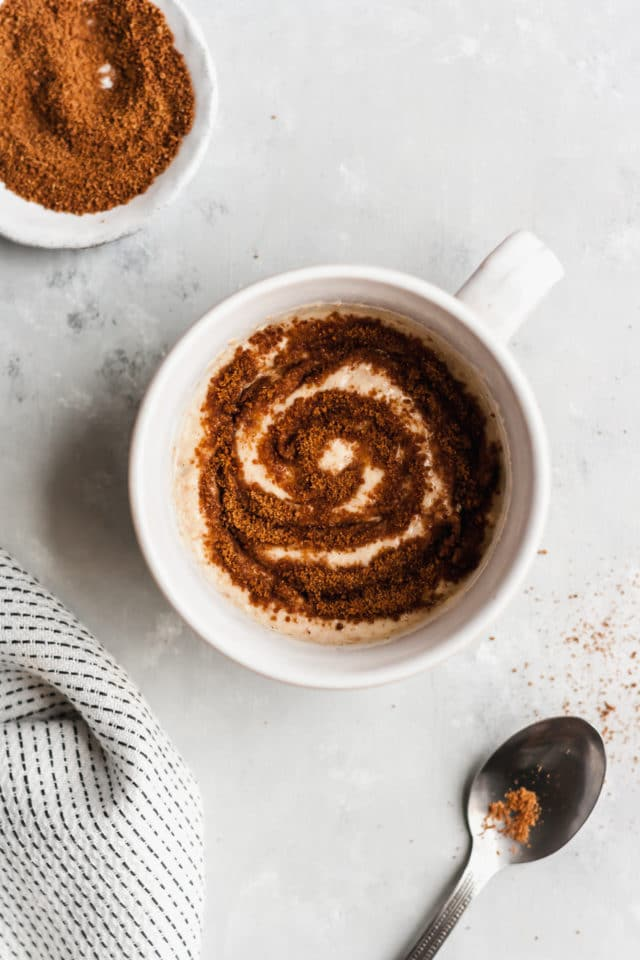 mug cake in a white mug with cinnamon topping swirled on top