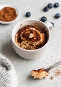 cinnamon roll microwave mug cake in a white mug with one spoonful taken out
