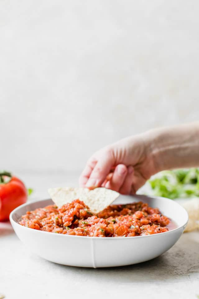 hand dipping salsa on a tortilla chip