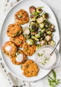 Sweet Potato Salmon Cakes served on a large white platter with Brussels sprouts and a dill dip