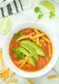 chicken tortilla soup served in a white bowl with lime and avocado slices