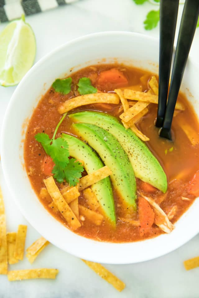 tortilla soup served in a bowl with two black spoons