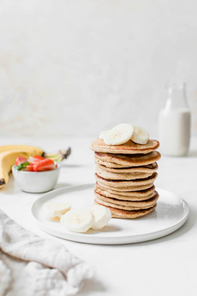 a stack of banana pancakes served on a white plate with sliced bananas and fresh strawberries