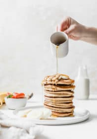 woman's hand pouring syrup over the top of a stack of pancakes
