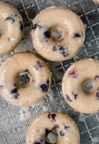 baked blueberry donuts topped with glaze on a wire cooling rack