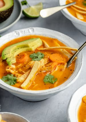 healthy chicken tortilla soup served with tortilla strips and slices of avocado