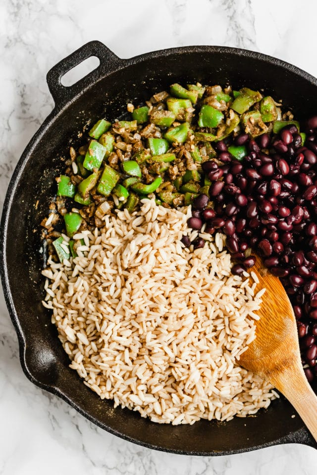 cooking rice, black beans and green bell pepper in a large cast iron skillet with a wooden spoon