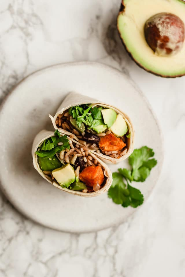 Sweet Potato Black Bean Burritos on a white plate garnished with cilantro