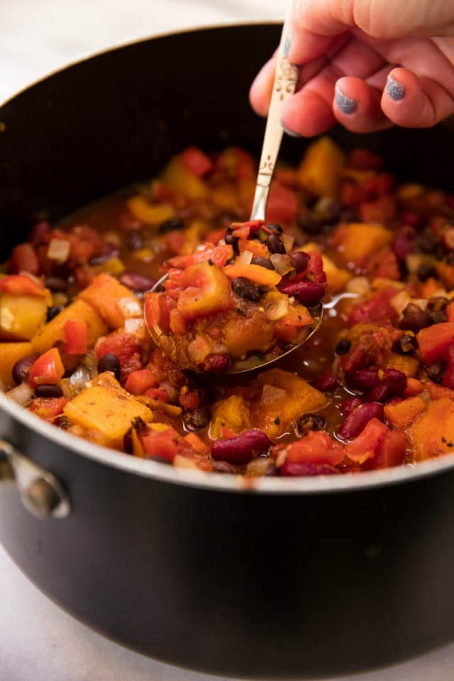 spooning out butternut squash black bean chili from a large pot