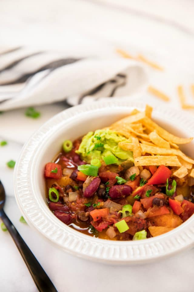 vegan bean chili topped with tortilla strips, green onion and guacamole