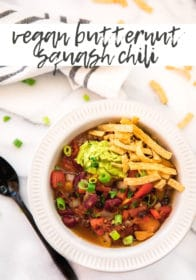 butternut squash chili in a white bowl topped with guacamole and tortilla strips