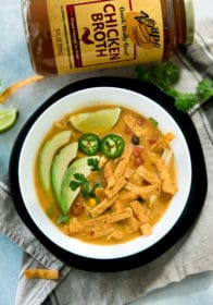 pumpkin chicken tortilla soup in a white bowl topped with avocado, lime, cilantro