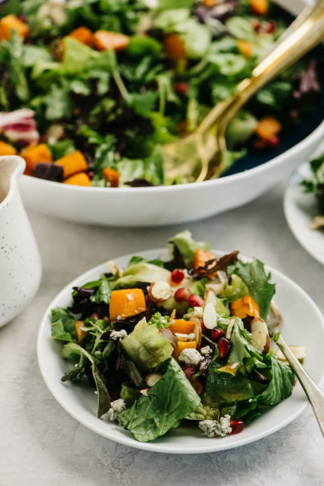 green salad topped with butternut squash and pomegranate seeds served in a small white bowl