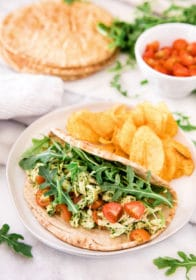 chicken salad in a pita with chips on a white plate