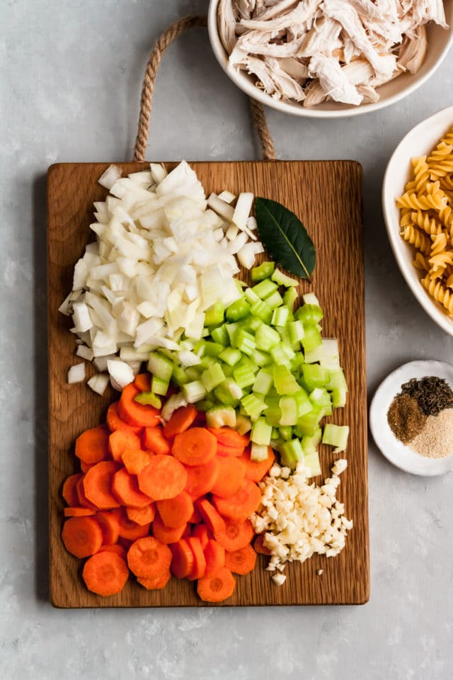 ingredients for chicken noodle soup on a wooden cutting board