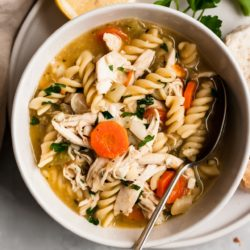 Chicken noodle soup with spoon in a white bowl and a lemon slice on the side