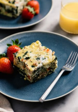 serving of egg casserole on a blue plate with strawberries and a fork