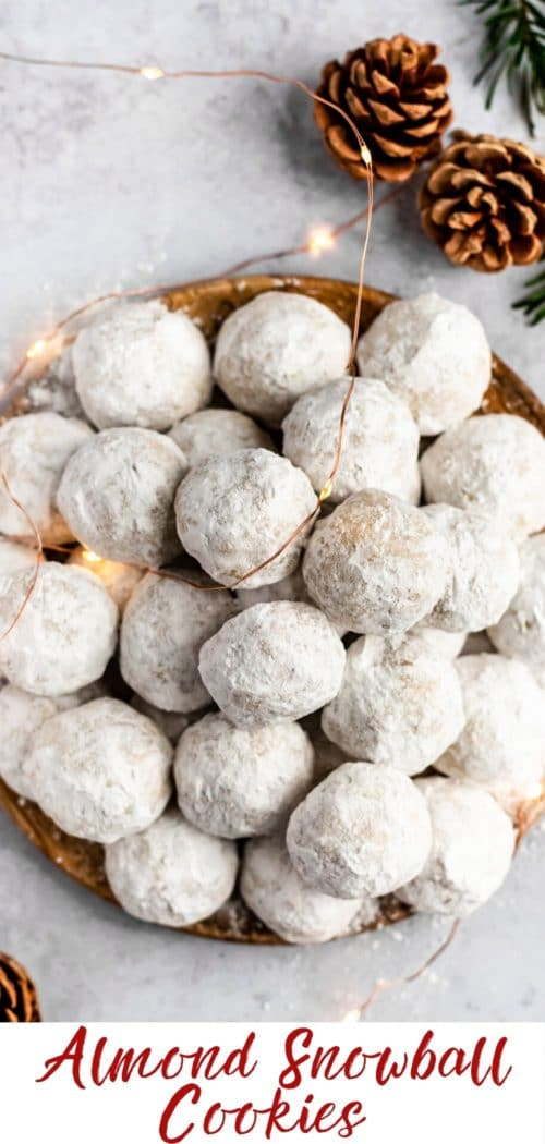 a plate filled with almond snowball cookies and Christmas lights