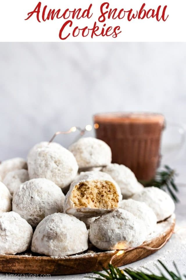 almond snowball cookies on a plate with a bite out of one