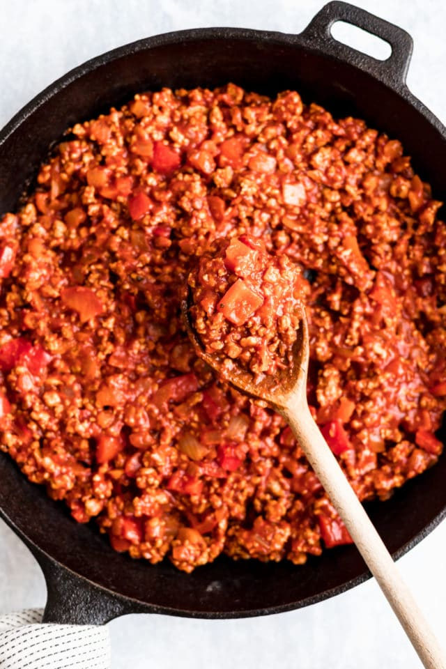 Healthy Sloppy Joes filling in a cast iron skillet with a wooden spoon