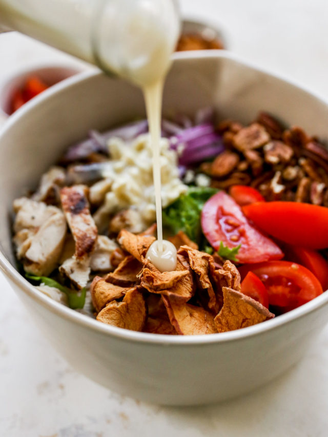 pouring dressing over a salad with grilled chicken