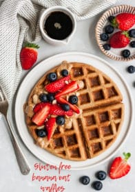large waffle on a white plate served with berries and syrup