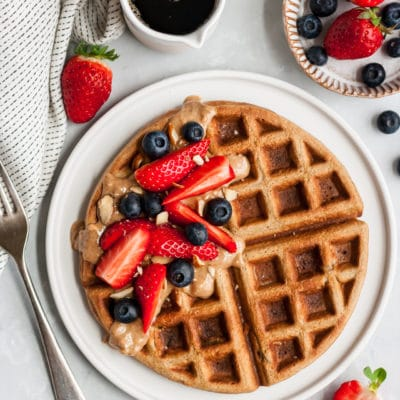 waffle on a white plate topped with fresh berries and almond butter