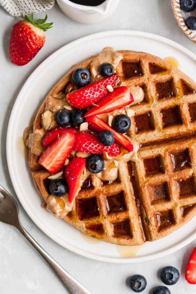 waffle on a white plate topped with sliced strawberries, blueberries, syrup and almond butter